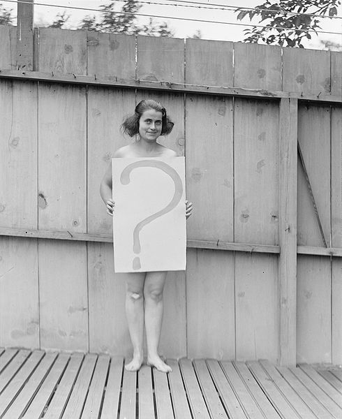 "Woman holding sign reading ""?"""